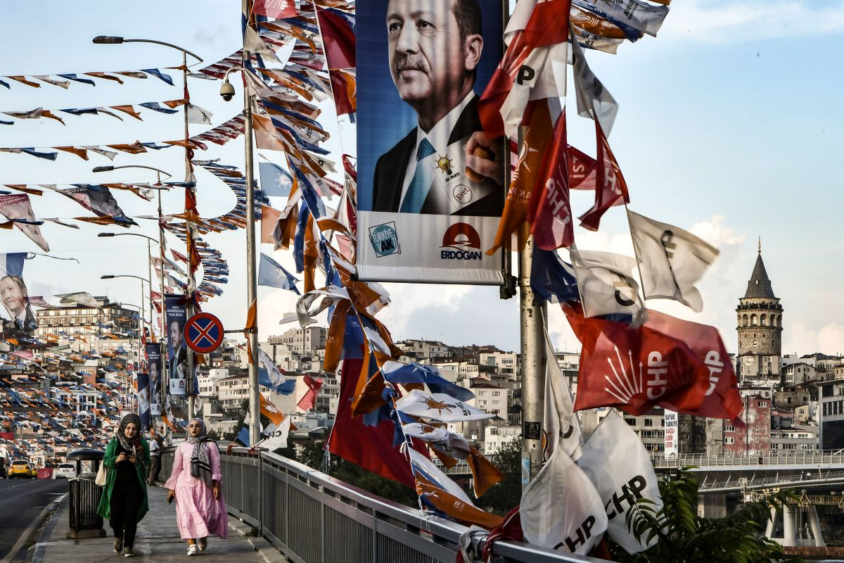 "Women walk on a bridge past campaign banners with the portrait of Turkey's president in Istanbul on June 18th, 2018. Turkey prepares for tight presidential and parliamentary elections on June 24th, while many analysts say President Recep Tayyip Erdogan wants a major foreign policy success to give him a final boost. The slogan reads ""A big Turkey wishes a powerful leader."""
