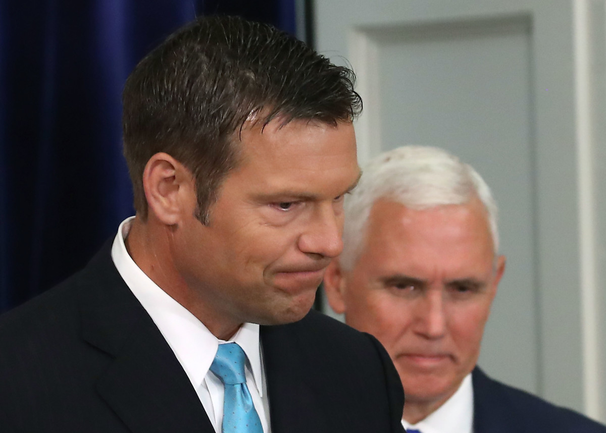 Kansas Secretary of State Kris Kobach (L) and U.S. Vice President Mike Pence attend the first meeting of the Presidential Advisory Commission on Election Integrity in the Eisenhower Executive Office Building.