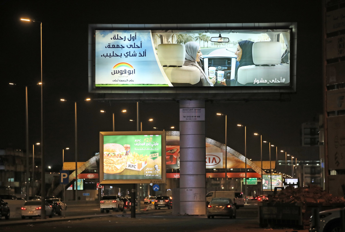 A commercial advertising billboard shows two women in a car with one behind the wheel on June 21st, 2018, in Jeddah.