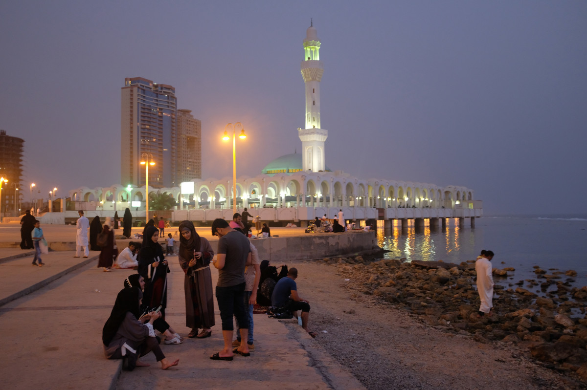 People relax on a Friday evening along the Corniche waterfront as the Al Rahma mosque stands behind on June 22nd, 2018, in Jeddah.