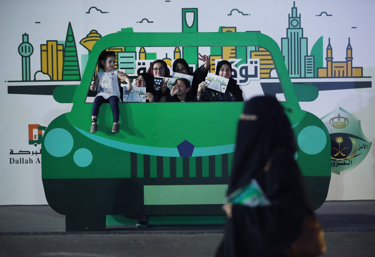 Teenage girls in Jeddah pose behind a model car on June 22nd, 2018, while holding up certificates for completing an outdoor educational driving event for women.