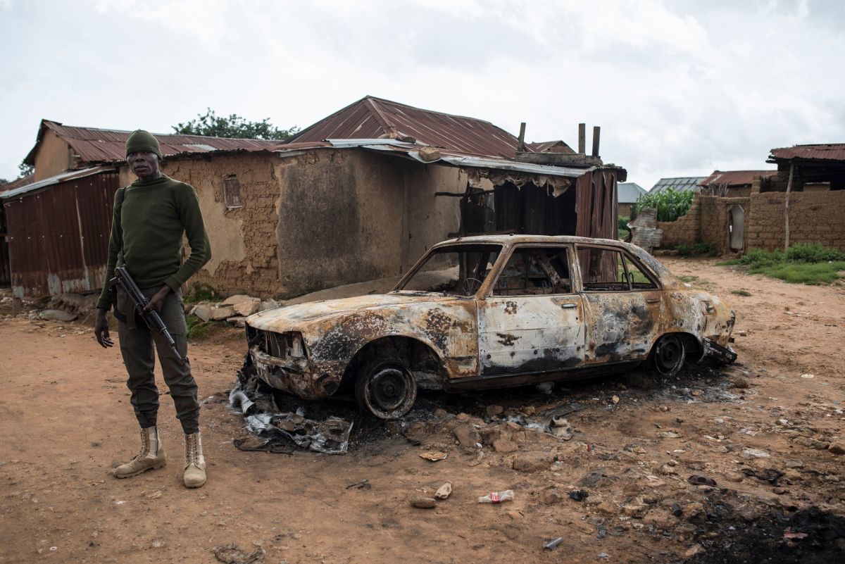 A member of the security forces stands next to a burnt vehicle in the Nghar Village, near Jos, on June 27th, 2018, after Fulani herdsmen attacked the village. Plateau State in Nigeria has seen days of violence where more than 200 people have been killed in clashes between Berom farmers and Fulani herders. Nigeria is facing an escalation in clashes between farmers and herders over land use and resources that is deepening along religious and ethnic lines.