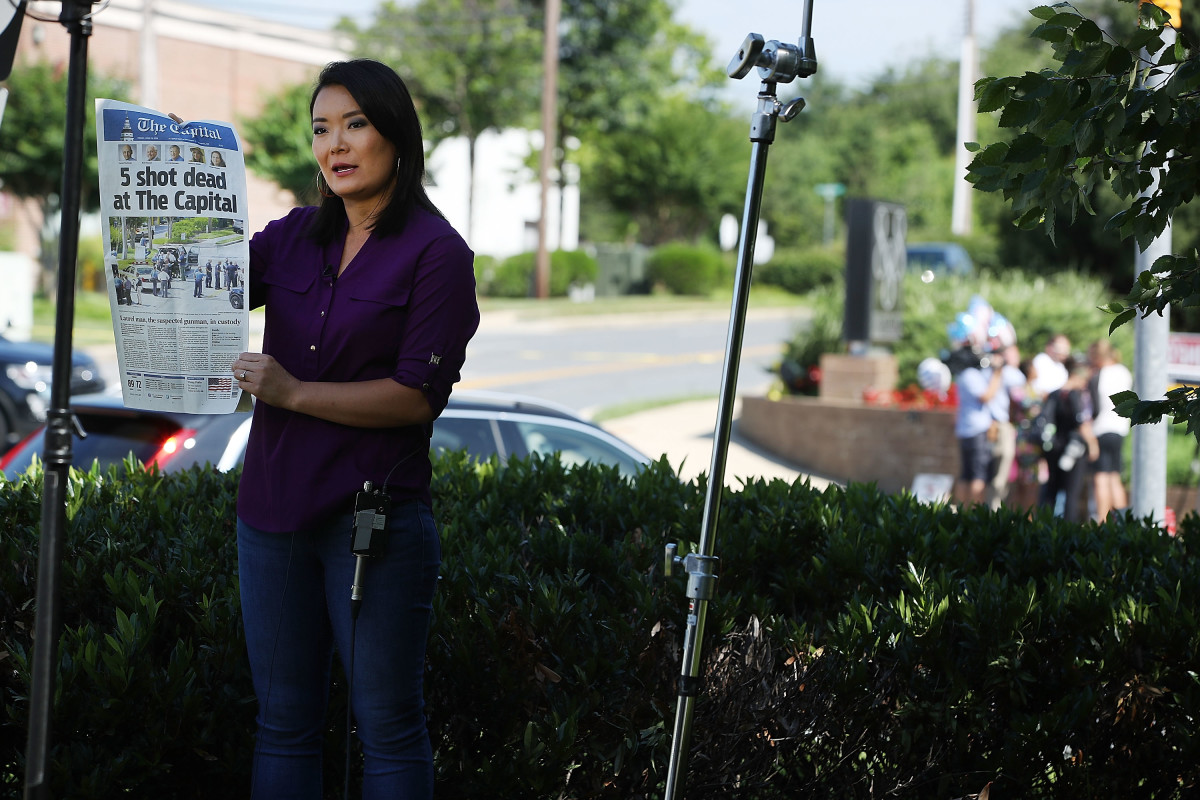 Television reporter Heidi Zhou-Castro holds up Friday's edition of the Capital Gazette, which appeared on newsstands the day after five of its employees were shot and killed by a gunman, on June 29th, 2018, in Annapolis, Maryland.