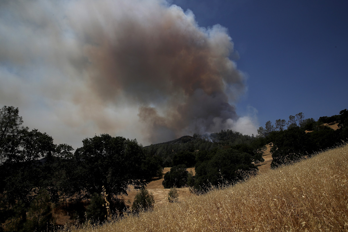 Smoke rises from the County Fire as it burns through dry brush on July 2nd, 2018, in Guinda, California.
