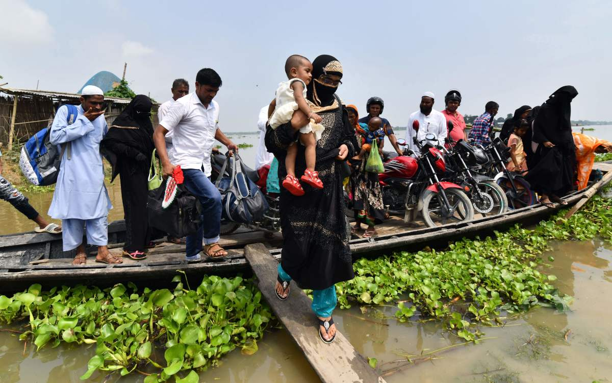 An Indian villager steps off a boat as she carries her child in flood-affected Ashigarh village in Morigoan district, in India's northeastern state of Assam, on July 6th, 2018. Heavy monsoon rains bring floods to parts of northeastern India each year, affecting the lives of millions of people.