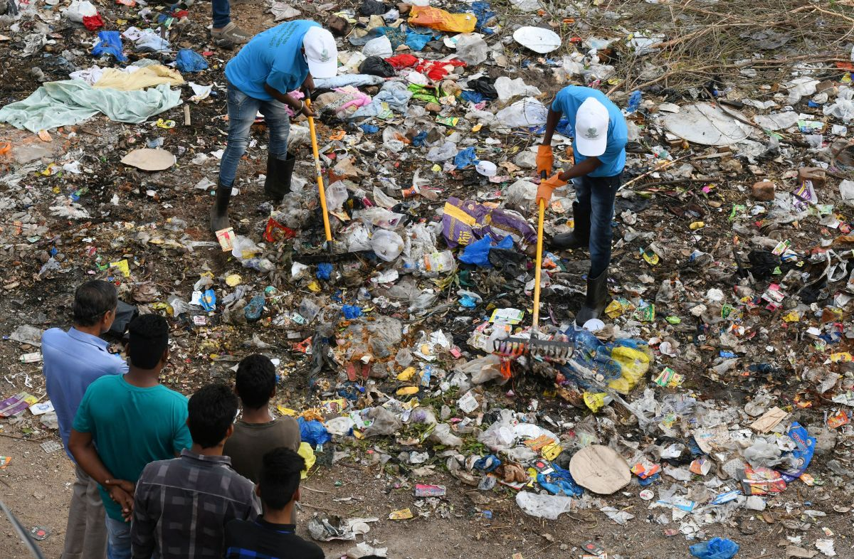 Indian residents look on as members of the National Green Corps clean up garbage along the Musi river in Hyderabad on June 3rd, 2018.