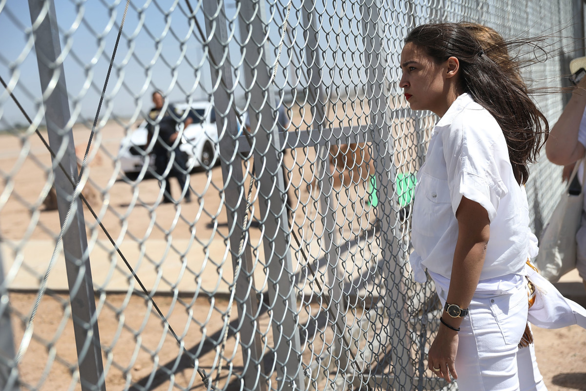 Alexandria Ocasio-Cortez stands at the Tornillo-Guadalupe port of entry gate on June 24th, 2018, in Tornillo, Texas.