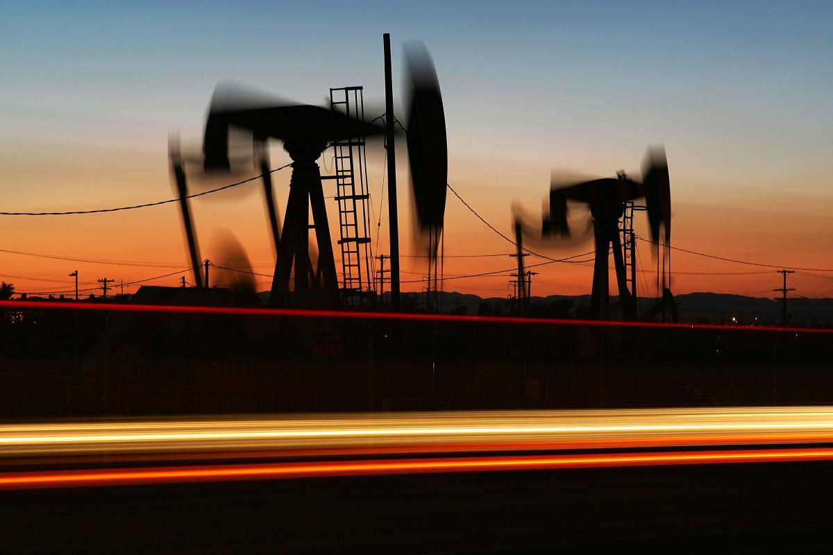 Car lights streak past an oil rig in Culver City, California.