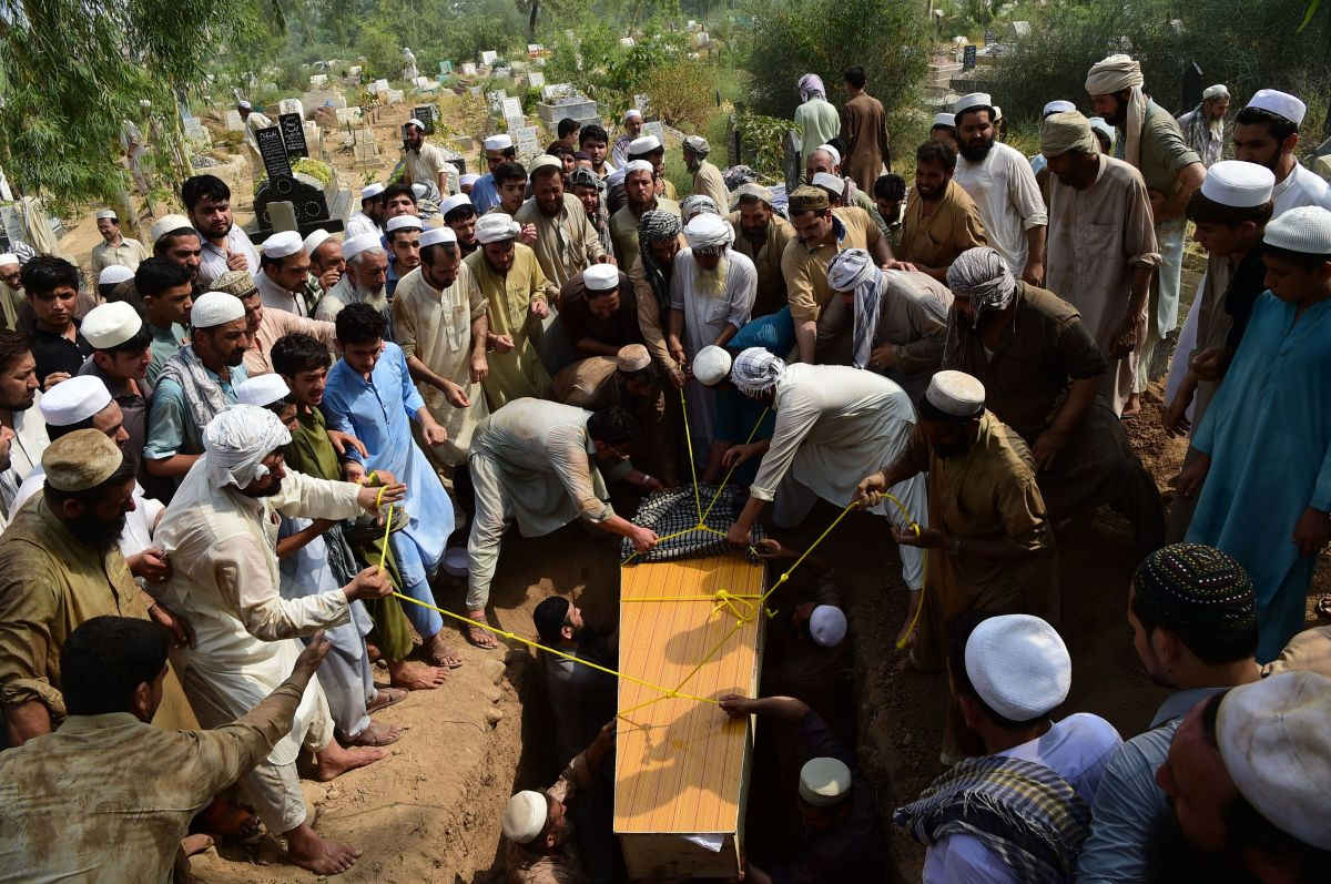 Pakistani residents bury a blast victim, killed in a suicide bombing at an election rally, during a funeral in Peshawar on July 11th, 2018.