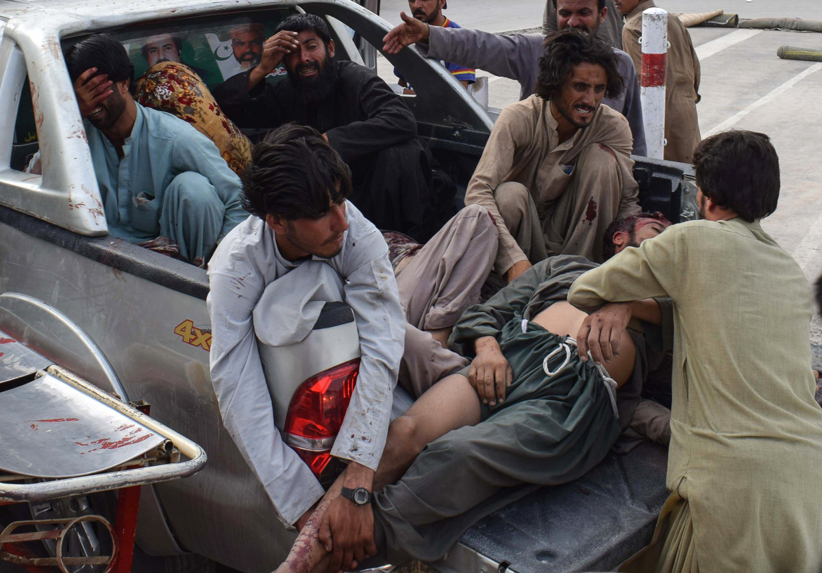 Pakistani men bring the victim of a bomb blast to a hospital in Quetta on July 13th, 2018.