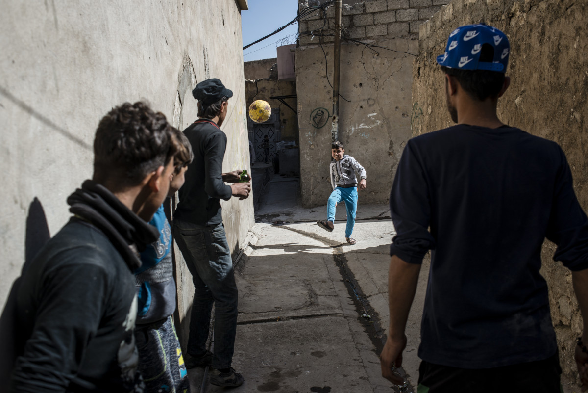 Ali, a boy who lost his arm in a mortar strike while his family was displaced, plays with his friends in the Old City once again.