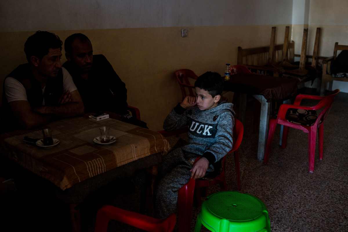 Dilshad sits in a cafe with his father and a family friend. He was recently released from ISIS captivity after his family bought him back.