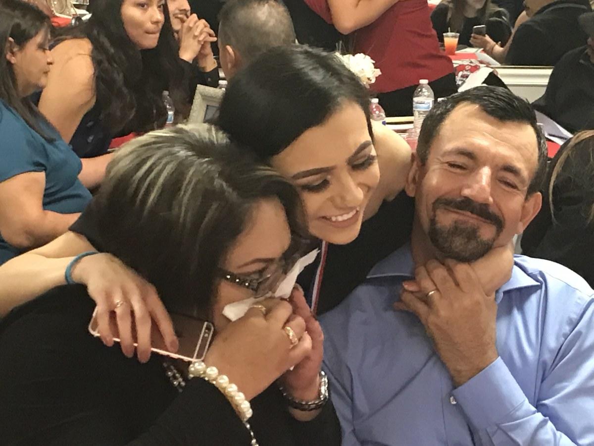 Julia Gomez-Delgado hugs her parents.