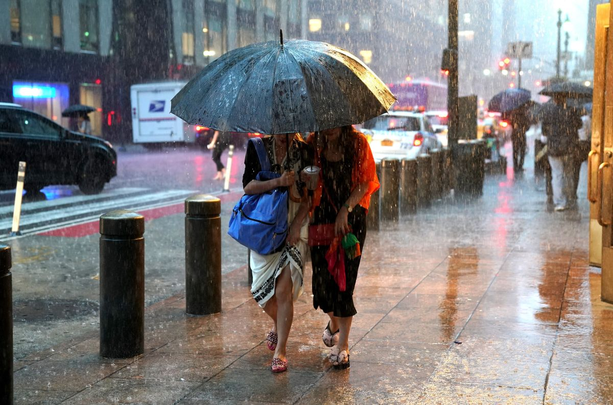 People take cover from the rain in Midtown New York on July 17th, 2018, as a sudden storm hit the area with flash food warning in the Tri-State area.