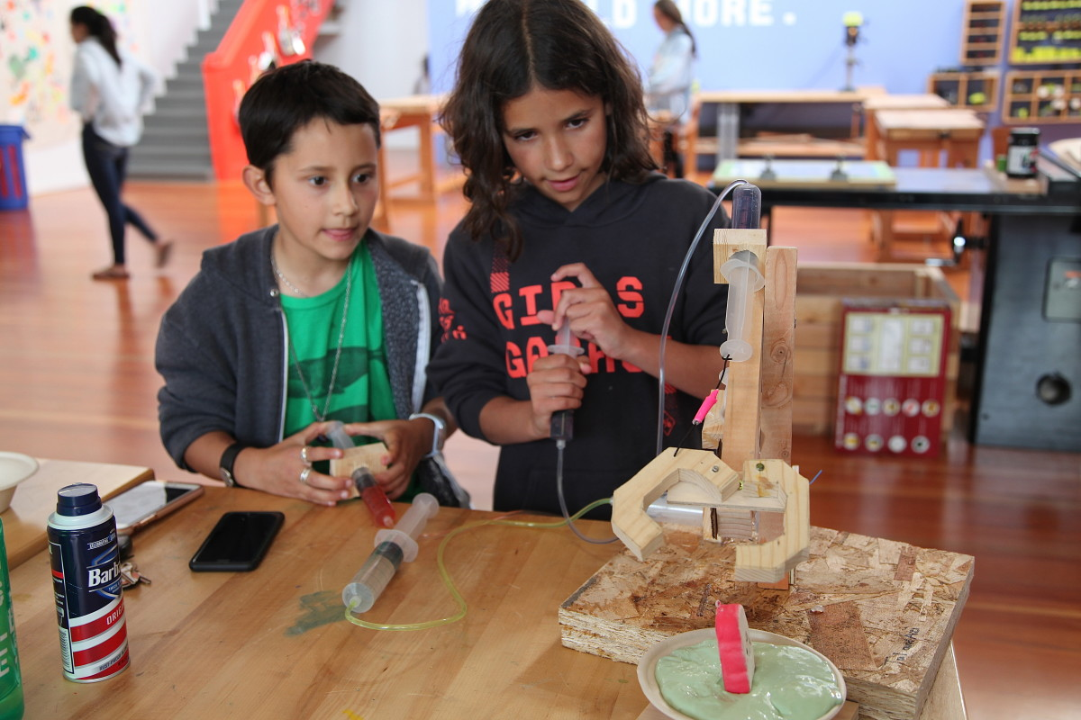 Azi, nine, (left) and Tal, 11, attempt to pull a squishy toy from a bowl of slime using the mechanical claw they constructed at a workshop at Girls Garage, in Berkeley, California.