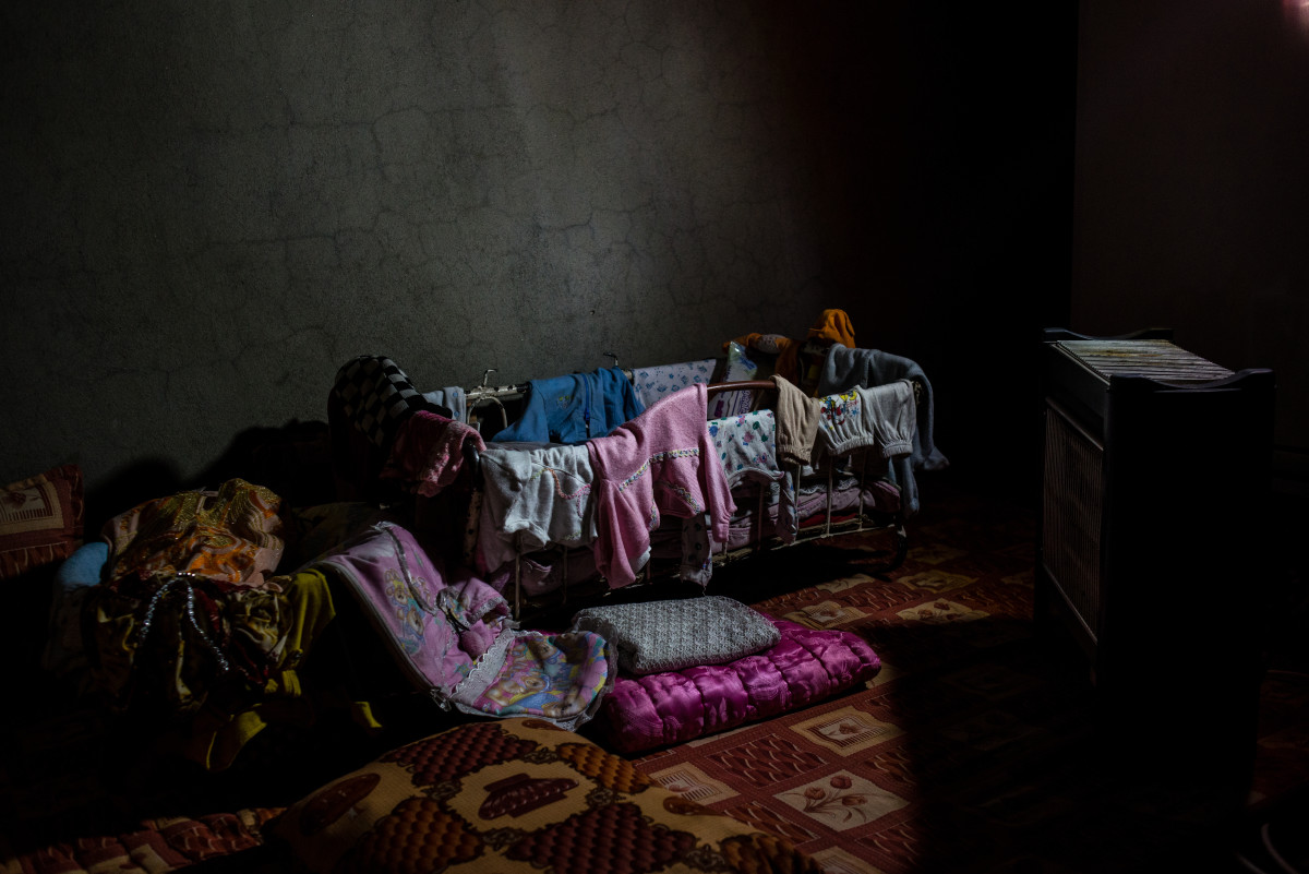 A mother holds a light to show the clothes of her granddaughter, who was killed while fleeing across the frontline—along with everyone else from her family, except for her son.