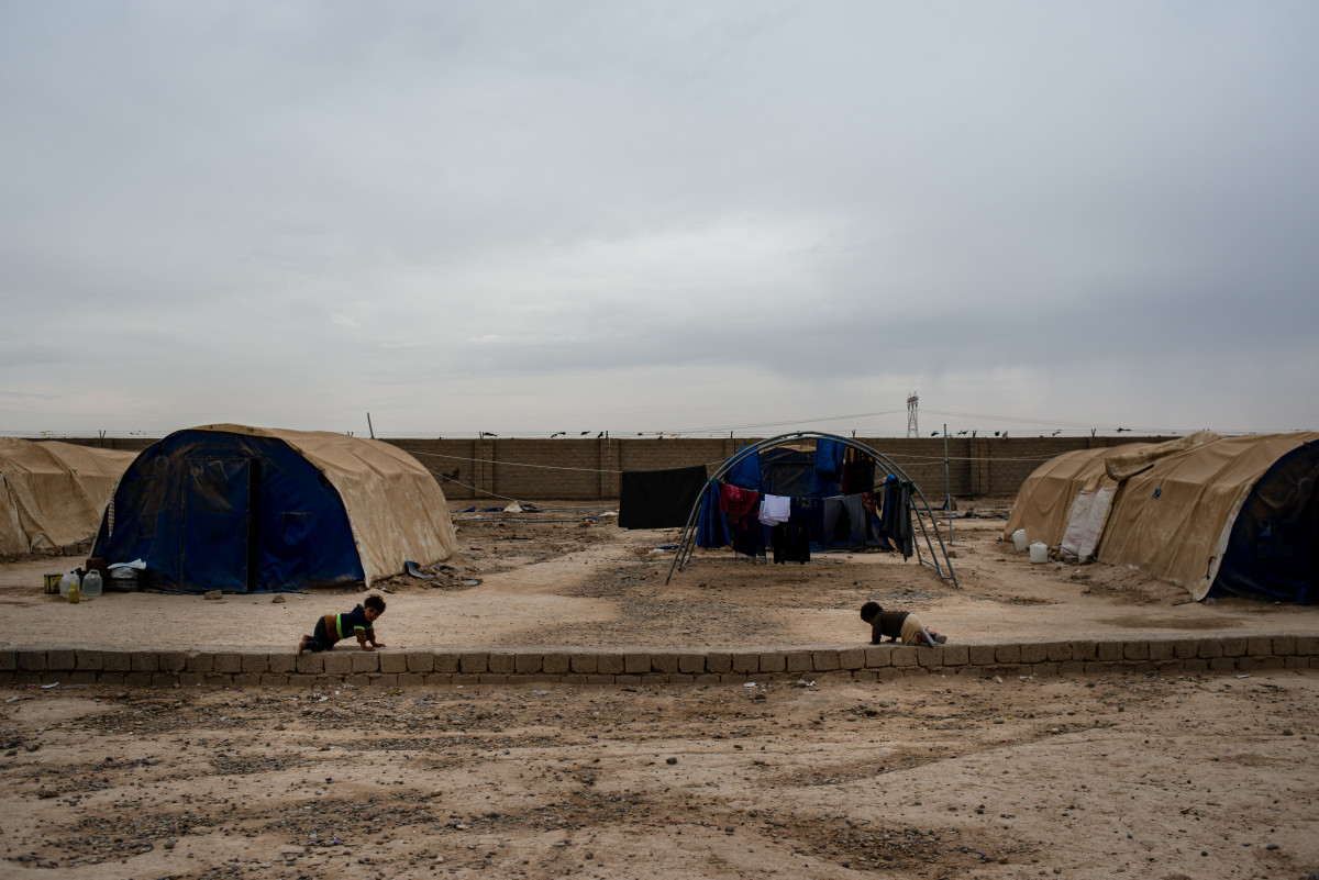 Babies crawl along cinder blocks in Shahama camp outside Kirkuk. The camp holds families with suspected ties to ISIS.