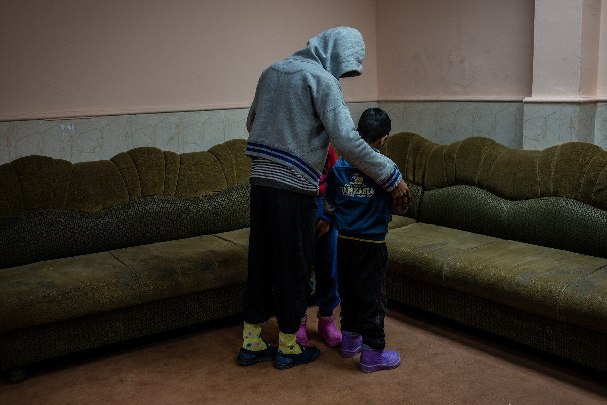 Two disabled boys, found wandering around playground city alone, are shielded by an older resident at the Mosul orphanage.