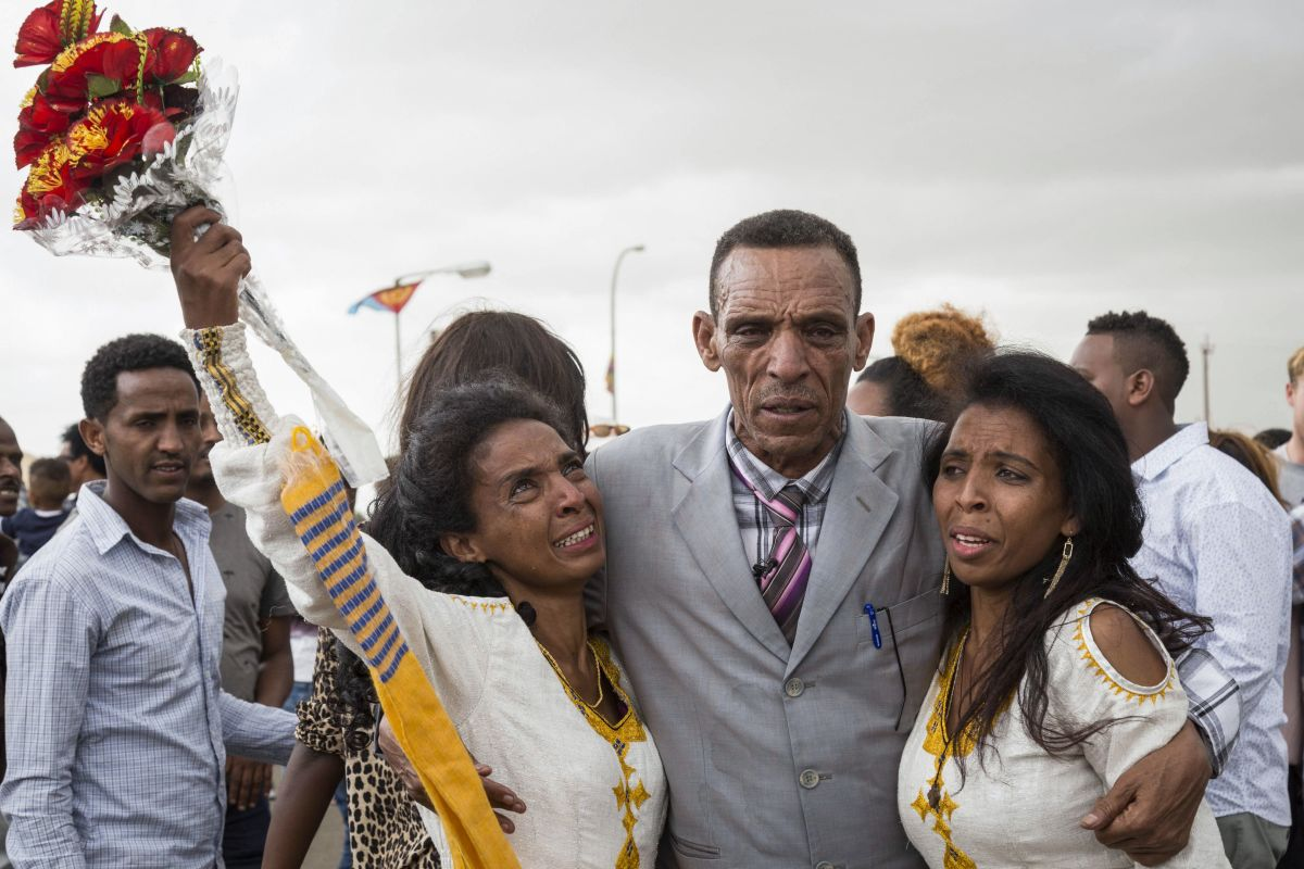 Azmera Addisalem and Danait Addisalem greet their father, an Ethiopian journalist, for the first time in 20 years, upon his arrival at the Asmara International Airport on July 18th, 2018.
