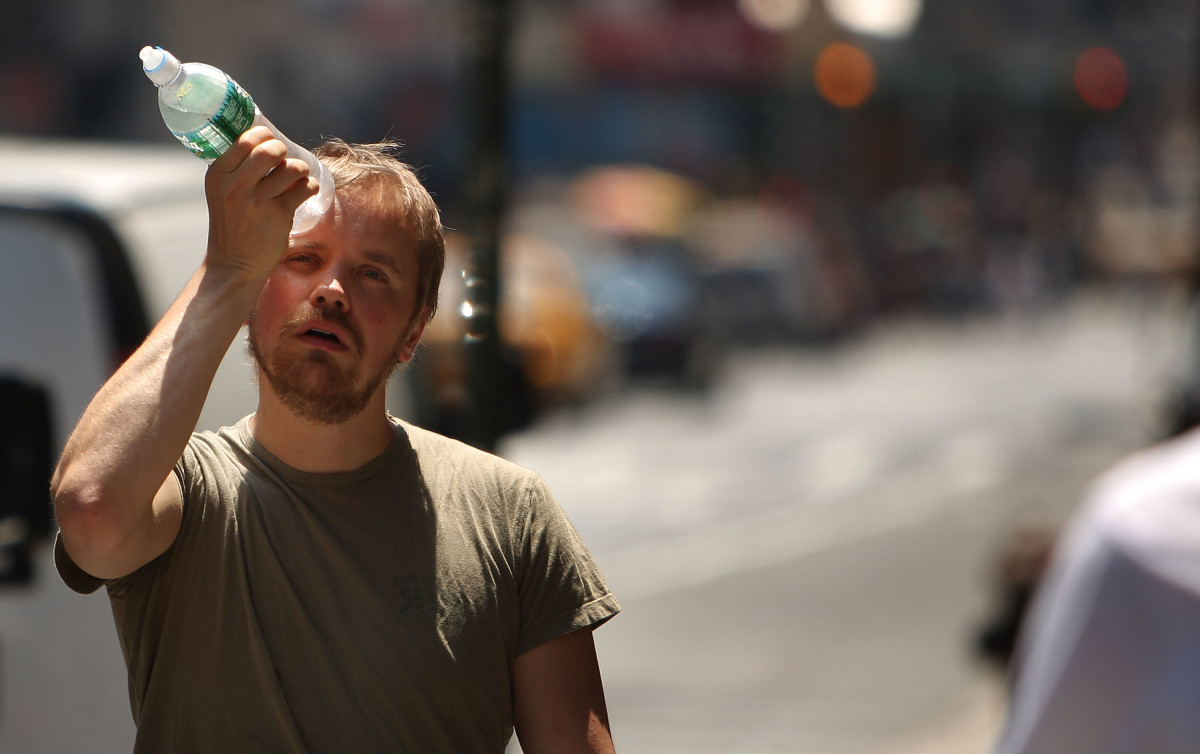 A man tries to cool himself with a bottle of water during a heat wave on June 9th, 2008, in New York City.