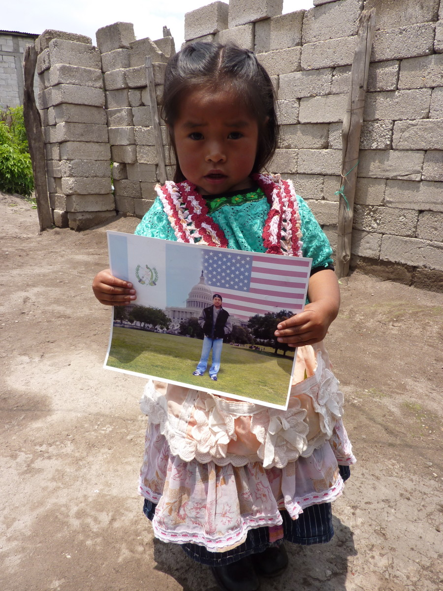 A young girl holds a photograph of her father, who died while trying to cross into the U.S.