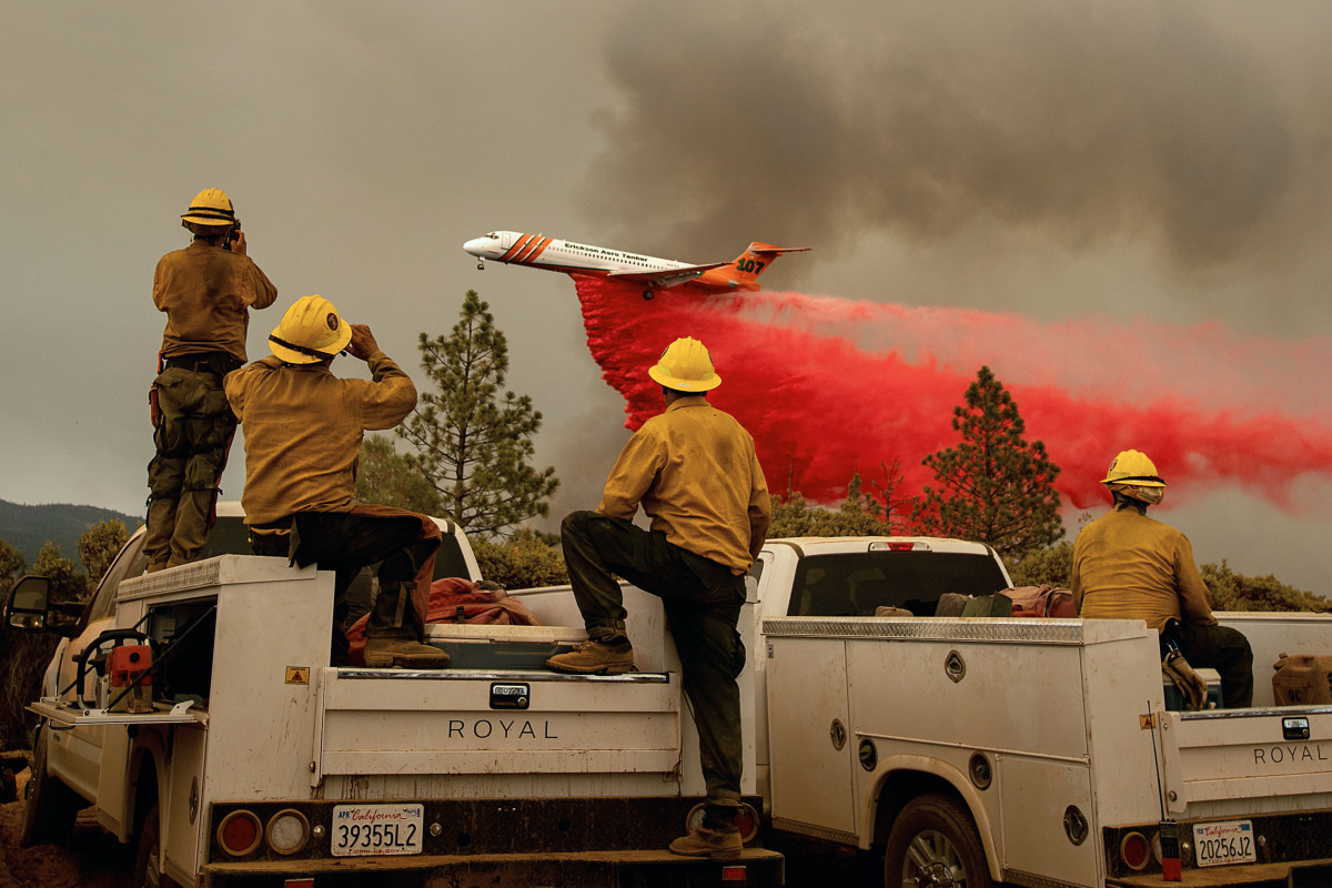 Firefighters watch as an air tanker drops fire retardant over the Ferguson Fire in the Stanislaus National Forest, near Yosemite National Park, on July 21st, 2018.