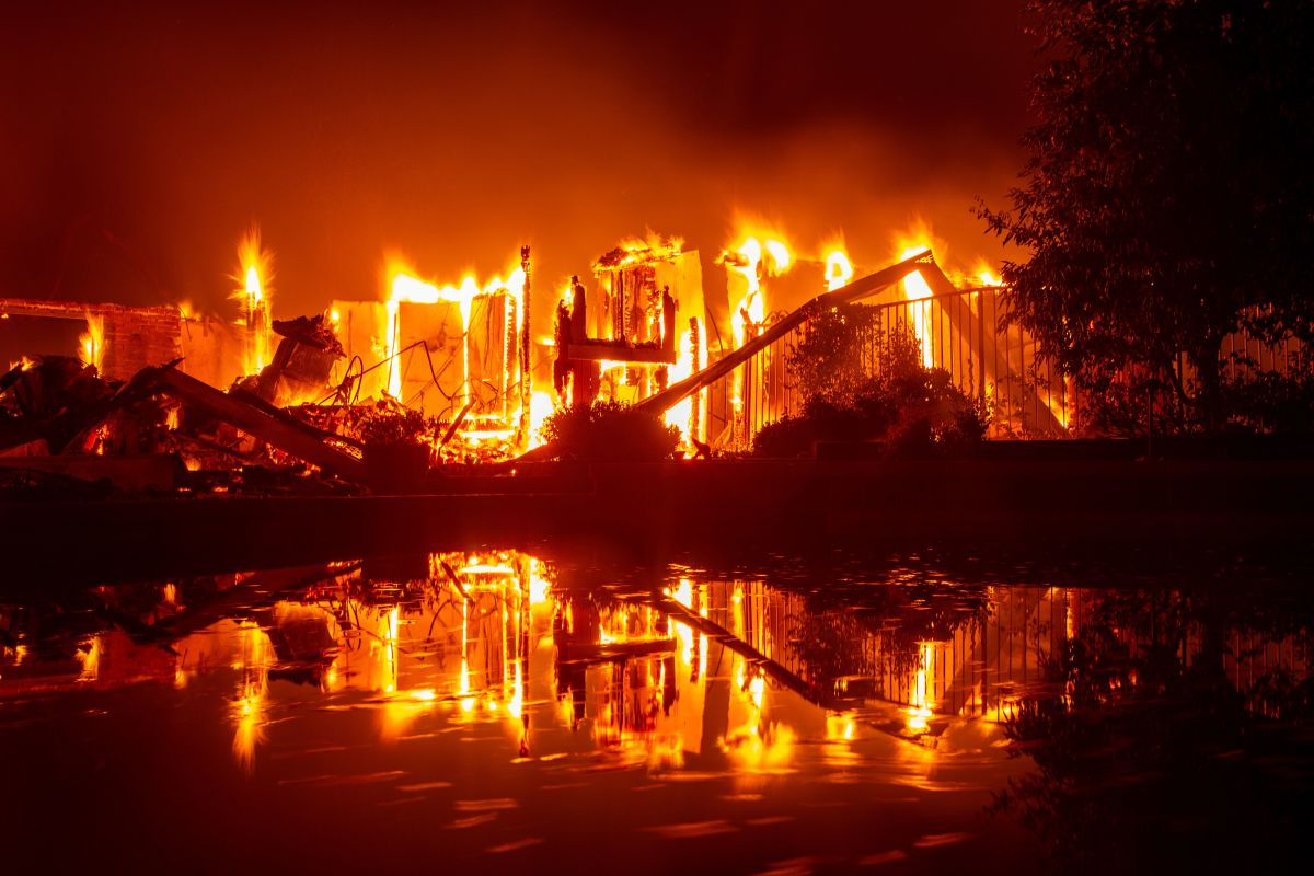 A burning home is reflected in a pool during the Carr fire in Redding, California, on July 27th, 2018.