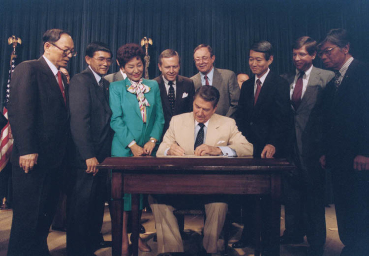 President Ronald Reagan signs the Civil Liberties Act of 1988 on August 10th, 1988, which granted reparations for the internment of Japanese Americans.