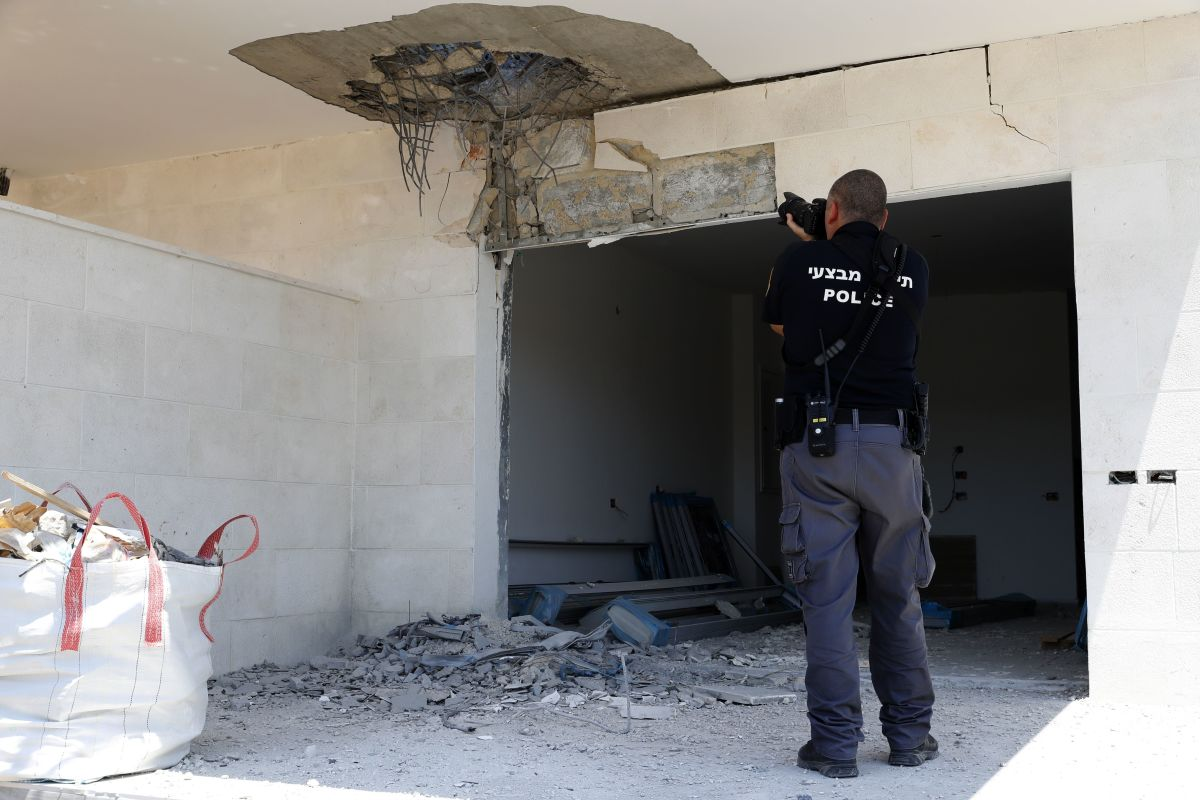 An Israeli policeman takes pictures on August 9th, 2018, of the damage in an empty house after a rocket fired by Palestinian militants from the Gaza Strip fell in the southern Israeli town of Sderot.