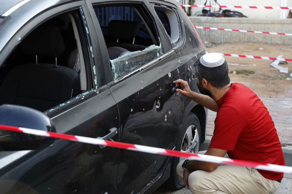 An Israeli man checks damage to his car after a rocket fired by militants from the Gaza Strip fell nearby in the southern Israeli town of Sderot on August 9th, 2018.