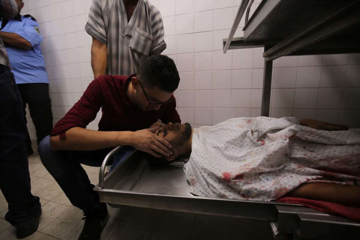 A relative of Palestinian paramedic Abdullah al-Qotati, who was killed while trying to help wounded protesters at the Israel-Gaza border, reacts over his body at a hospital in Khan Yunis in the southern Gaza Strip on August 10th, 2018.