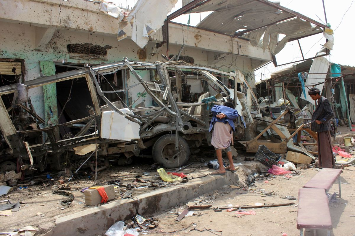Yemenis gather next to the destroyed bus at the site of a Saudi-led coalition airstrike, on August 10th, 2018.