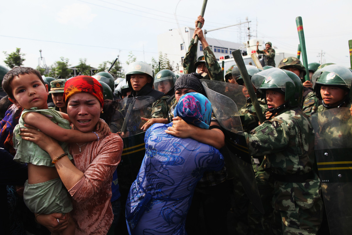 Chinese policemen push Uighur women who are protesting at a street on July 7th, 2009, in Urumqi, China.