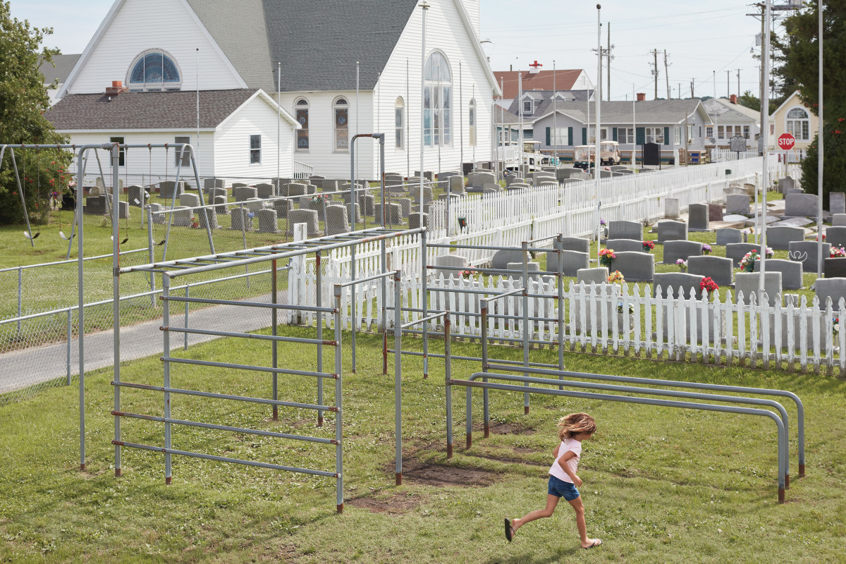 Jordan Daley stretches her legs in Tangier Island's public playground. During high tide, standing water pools beneath the jungle gym.