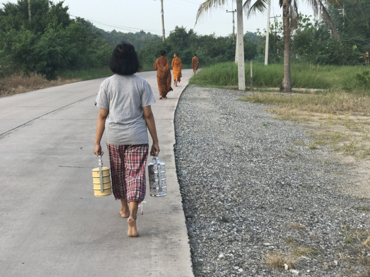 A young Thai girl follows three novice monks in the collection of the morning alms, in which they accept donations of food and drink to the temple from residents throughout the village of Chonburi.