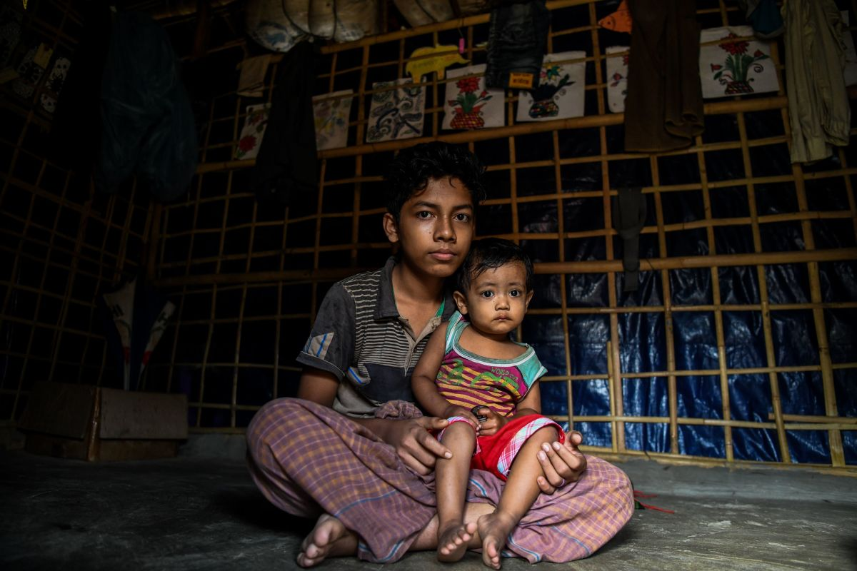 Rohingya refugee boy Kamal Sadiq, 14, holds his cousin, Ruma Sadiq, inside his home at the Kutupalong camp in Ukhia on August 13th, 2018.