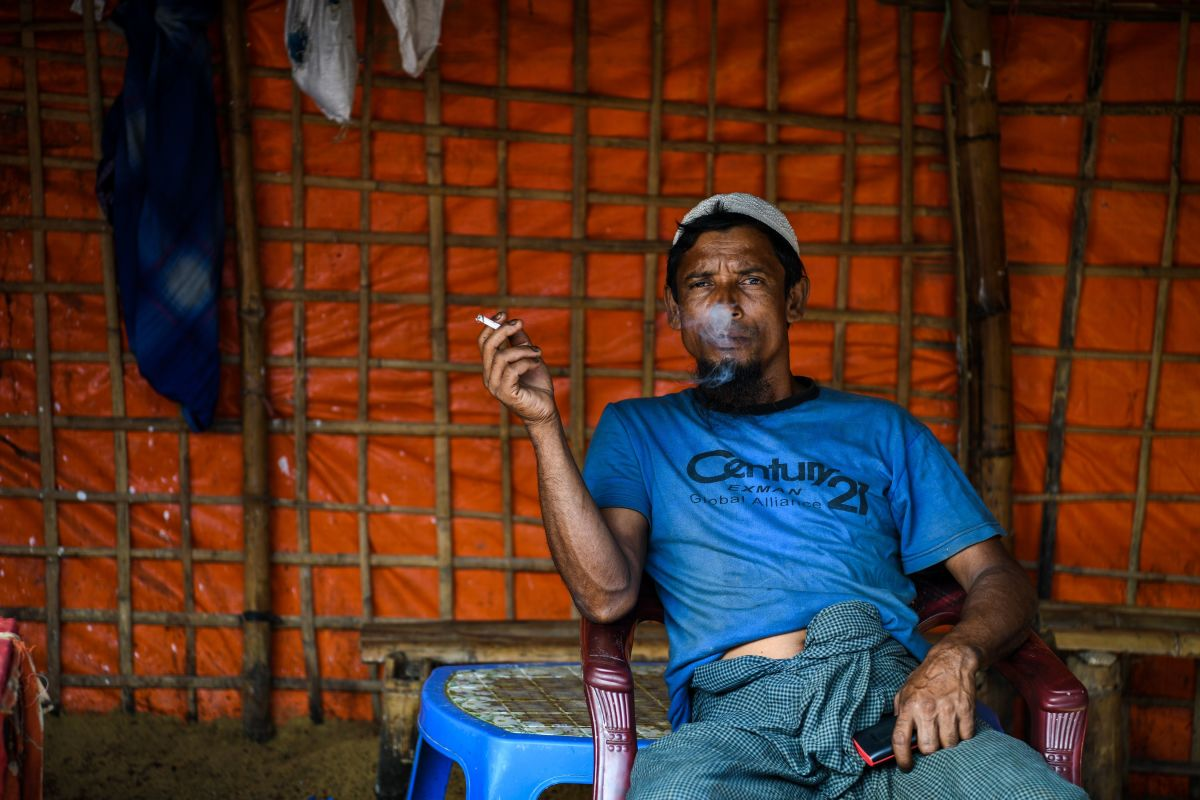 A Rohingya refugee man smokes inside a local food joint in the Kutupalong refugee camp in Ukhia on August 14th, 2018.