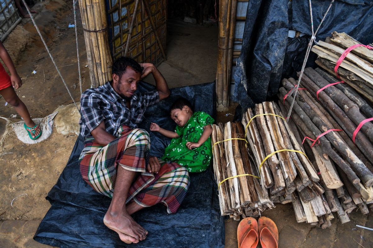 A Rohingya refugee plays with his daughter by the entrance of their tent at the Kutupalong camp in Ukhia, near the city of Cox's Bazar, on August 13th, 2018. Nearly 700,000 Rohingya fled Myanmar's Rakhine state last year to escape a violent military crackdown.