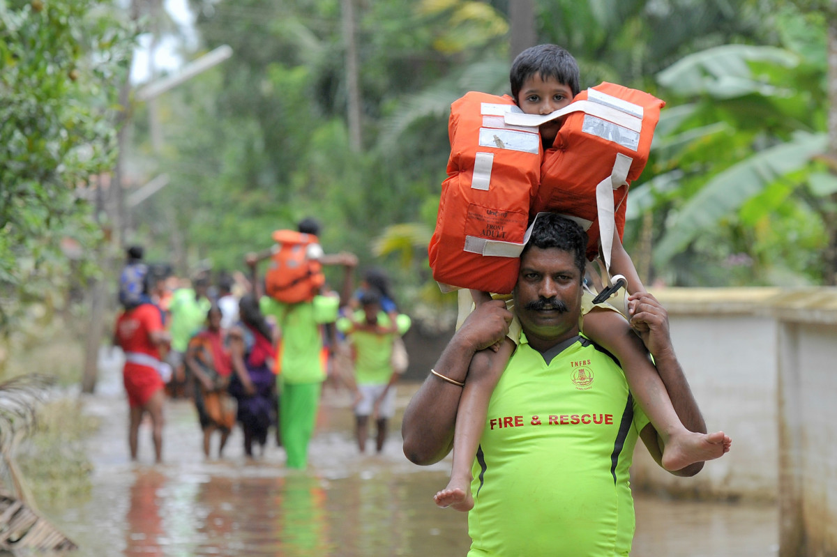 Rescue personnel carry children on their shoulders through flood waters during a rescue operation in Annamanada, a village in India, on August 19th, 2018. Rescuers waded into submerged villages in a desperate search for survivors cut off for days by floods that have already killed more than 350 people.