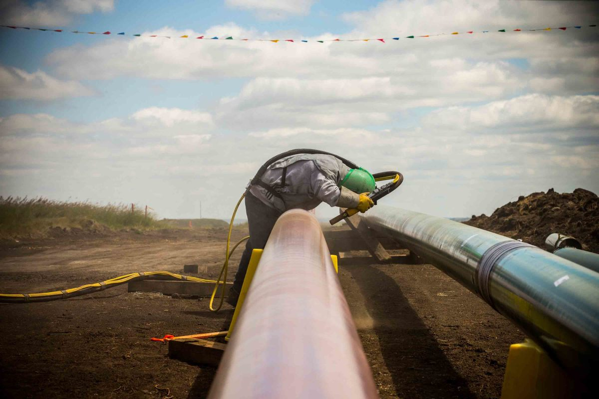 A construction worker specializing in pipe-laying sandblasts a section of pipeline on July 25th, 2013, outside Watford City, North Dakota.