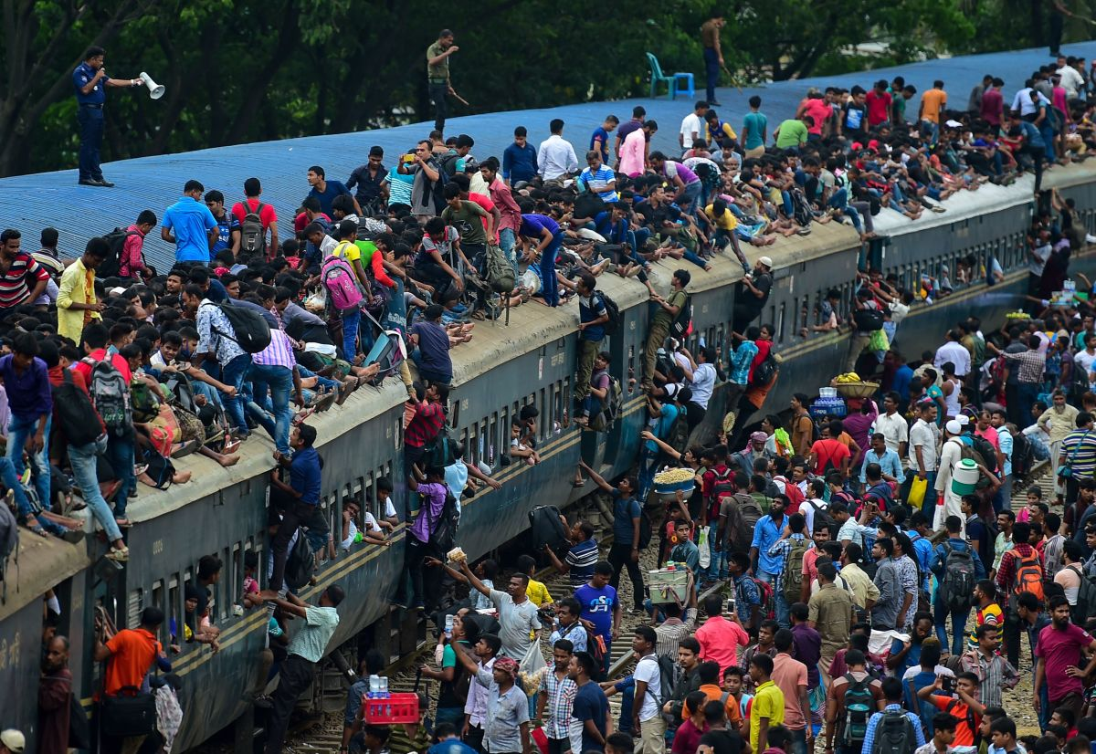 People scramble to reach the roof of an overcrowded train at a station in Dhaka, Bangladesh, on August 20th, 2018. Crowds rushed home from the capital city to be with friends and family during the annual holiday of Eid al-Adha, also known as the Festival of Sacrifice, celebrated by Muslims worldwide.