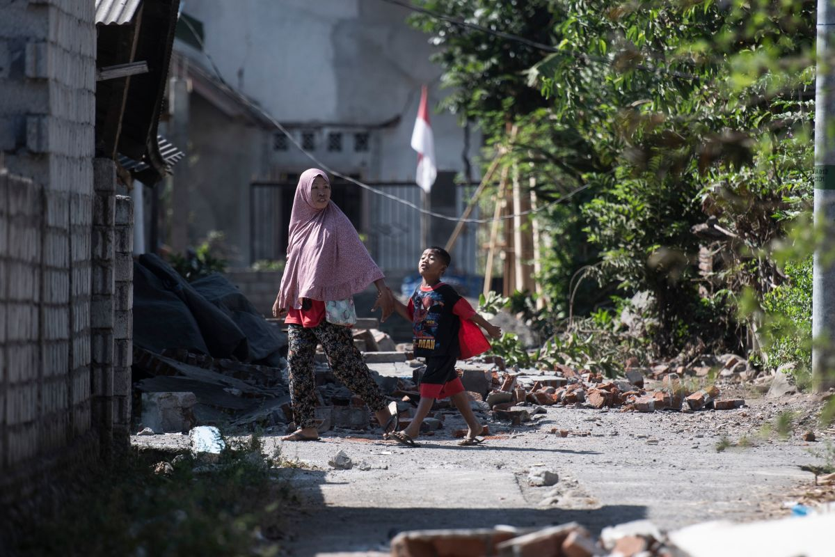 Residents walk among debris in the village of Sugian on Indonesia's Lombok Island on August 21st, 2018, after a series of recent earthquakes. Indonesian aid agencies and government officials rushed to help survivors after another series of powerful quakes rattled the island, killing at least 14 people and leaving hundreds of thousands homeless.