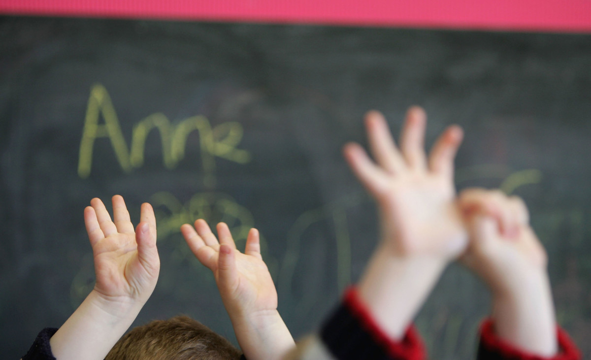 Children wave their hands at a private nursery school in Glasgow, Scotland.