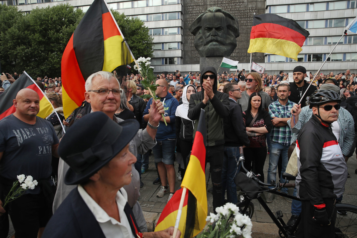 People holding German flags arrive at a right-wing protest gathering near a statue of Karl Marx the day after a man was stabbed and died of his injuries on August 27th, 2018, in Chemnitz, Germany. A German man died after being stabbed in the early hours of August 26th following an altercation, leading a xenophobic mob of approximately 800 people to take to the streets. Left- and right-wing groups of over a thousand people each confronted each other as riot police stood in between.