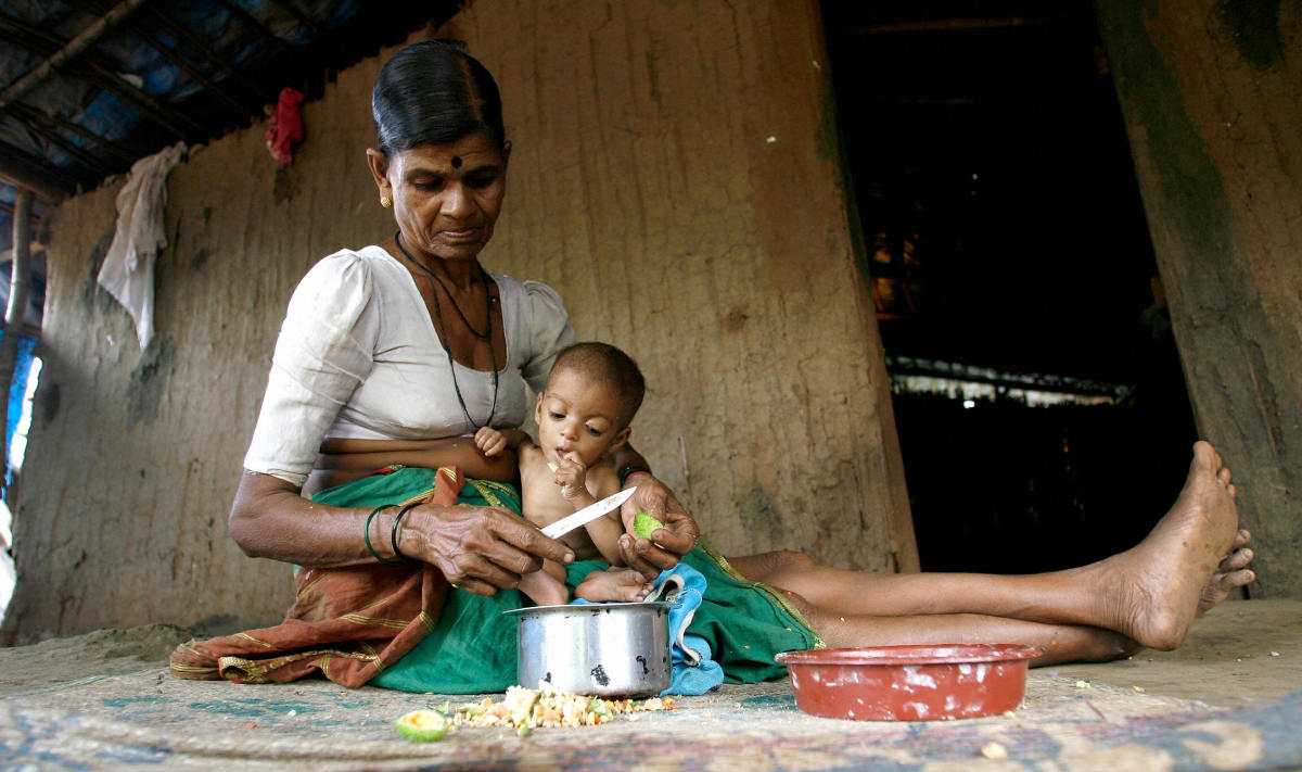 Hira Bai takes care of her grandchild Rohit in their mud and bamboo reinforced hut in Devipada, a tribal settlement in the remote forestland of Aarey Milk Colony on the outskirts of Mumbai.