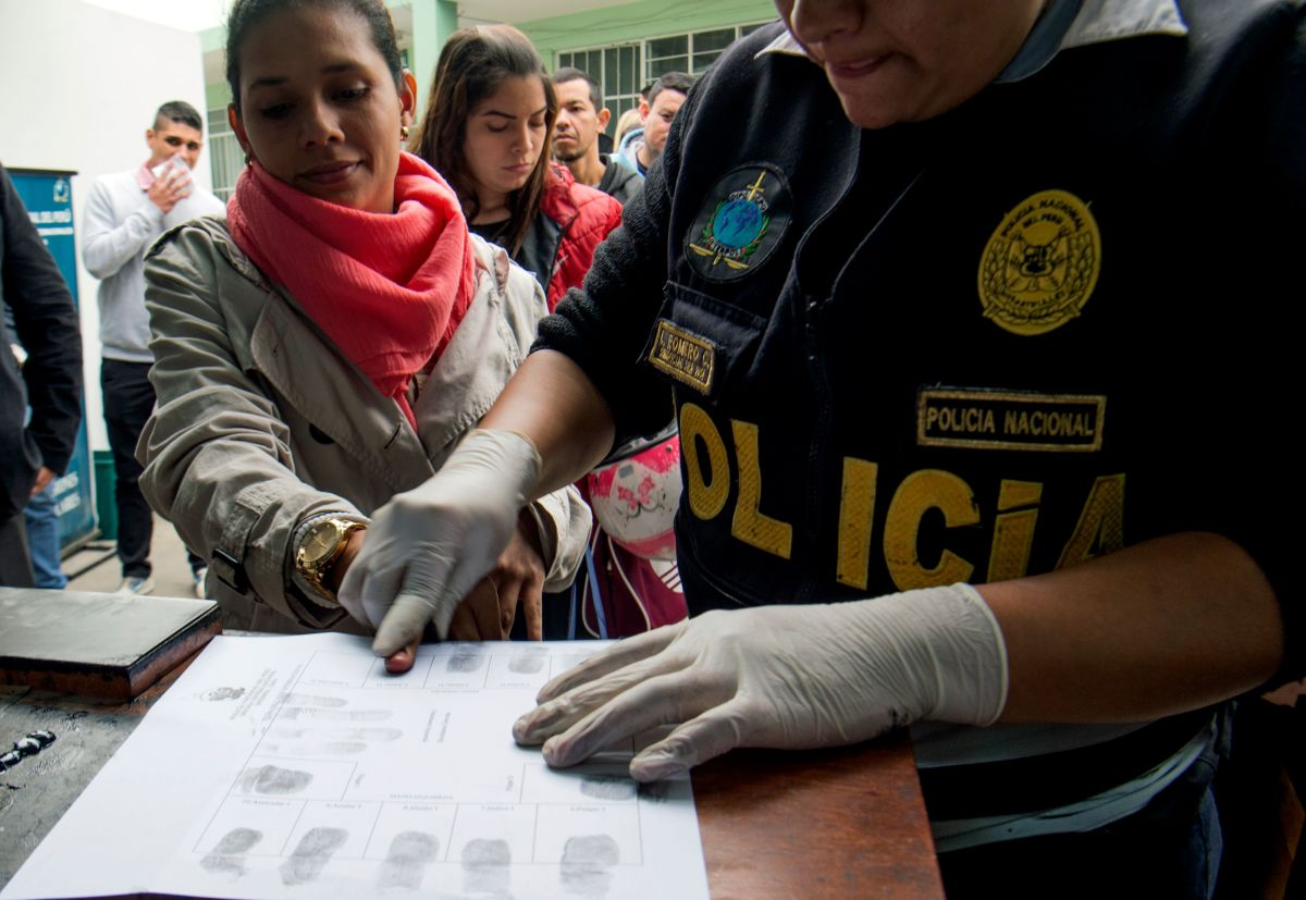 A policeman takes fingerprints of a Venezuelan migrant as a group of migrants wait to apply for resident visas or temporary stay permits at an Interpol facility in Lima, Peru, on August 29th, 2018. Last Friday, Peru enacted rules that mandated that Venezuelans coming into the country show a passport (previously, the law only required an identification card). Since then, hundreds of Venezuelans have applied for asylum in Peru. As Venezuela suffers an unprecedented economic and humanitarian crisis, hundreds of thousands of Venezuelans have fled into other South American countries, escaping intolerable food and medicine shortages in their home country.