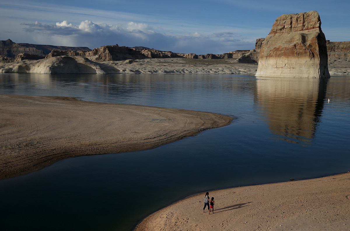 People walk on a beach that used to be the bottom of Lake Powell on March 29th, 2015, near Big Water, Utah. Lake Powell is one of the Colorado River Basin's two biggest reservoirs, along with Lake Mead.