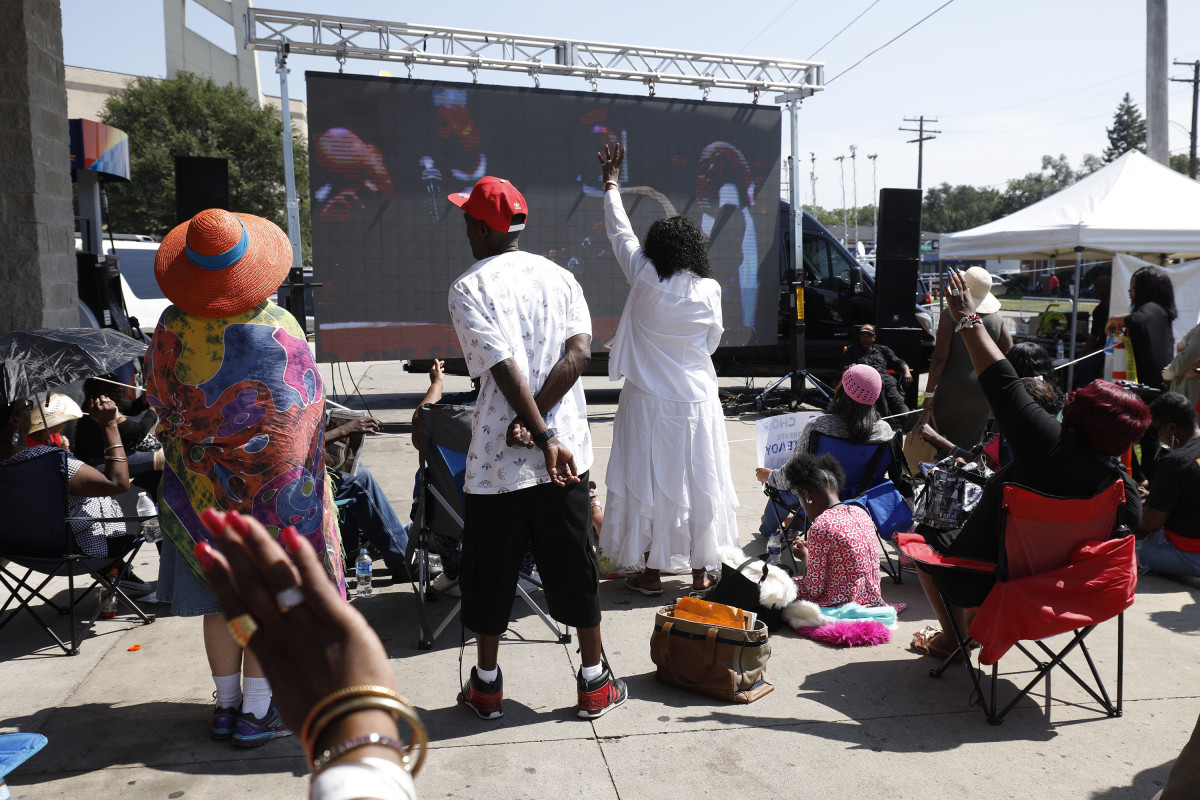 Fans of Aretha Franklin watch the singer's funeral on a giant screen outside Greater Grace Temple on August 31st, 2018, in Detroit, Michigan. Dozens of musicians and dignitaries spoke and performed at the singer's funeral, including former President Bill Clinton, Stevie Wonder, Ariana Grande, and Smokey Robinson.
