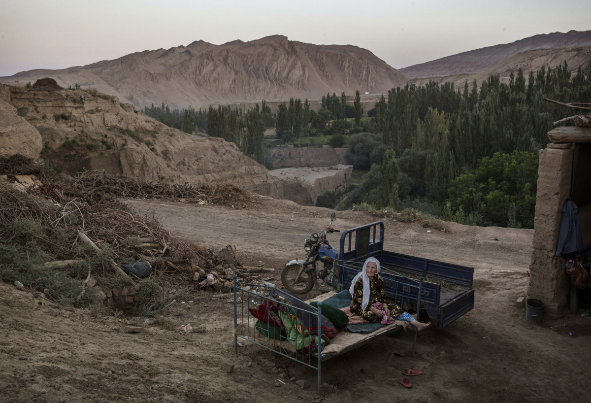 A Uyghur woman sits on a bed outside on September 12th, 2016, in Turpan County, in the far western Xinjiang province of China.
