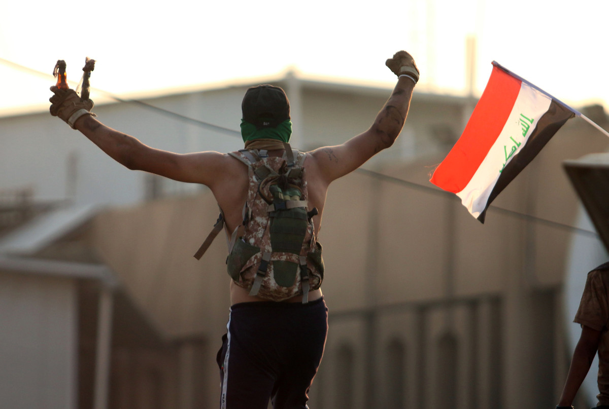 An Iraqi protester waves fire bombs during a protest outside the regional government headquarters in Basra on September 5th, 2018.